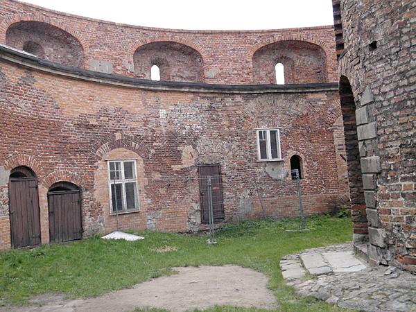 Wewnątrz twierdzy. Po lewej u góry, stanowiska artyleryjskie na wieńcu. Po prawej mur wieży (Fot. Joanna Piłat)