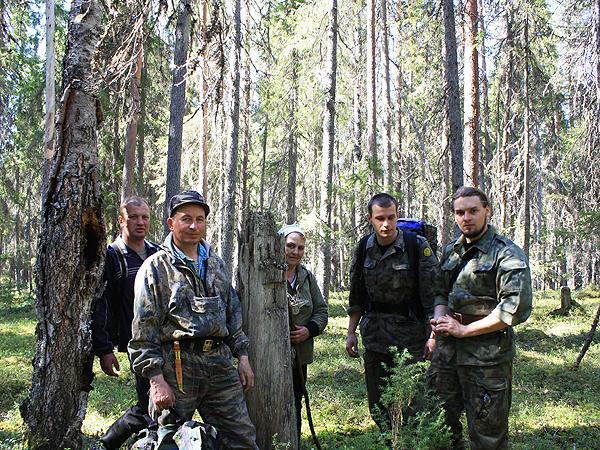 """Leśniczy Mikołaj (drugi od lewej) pokazuje drewniany słup z lat 40. wyznaczający sektory lasu (Fot. Adam """"Kaczor"""" Kaczyński)"""
