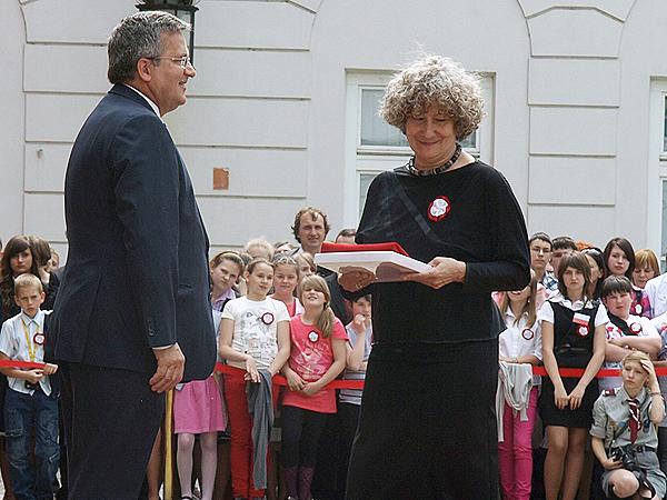 Prezydent Bronisław Komorowski wręcza Emilii Chmielowej polską flagę, Dzień Flagi 2012 r. (Fot. Mirosław Rowicki)