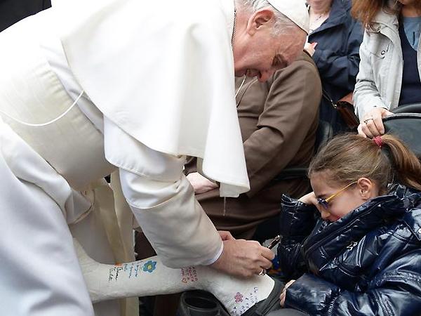Kiedy po audiencji papież kończył objazd placu Świętego Piotra w papamobile, kazał zatrzymać się w miejscu, gdzie znajdowali się niepełnosprawni i chorzy pielgrzymi. Wśród tłumu była siedząca na wózku dziewczynka z nogą w gipsie, ozdobionym rysunkami i podpisami. Papież Franciszek także zdecydował się podpisać na jej gipsie (Fot. se.pl)